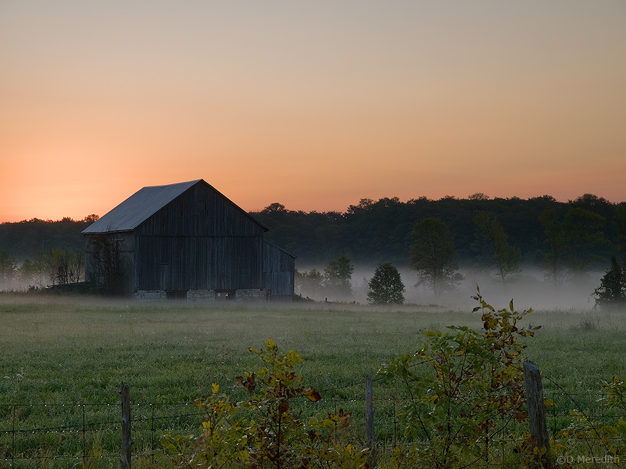 Old barn in mist at sunrise.
