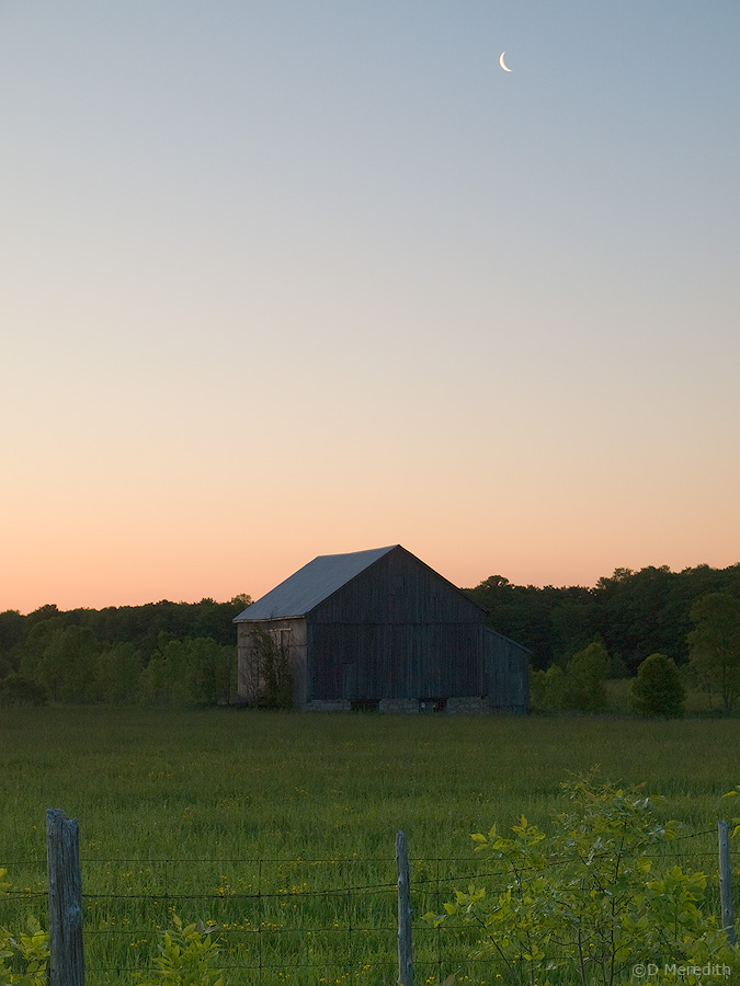 Crescent moon over an old barn.