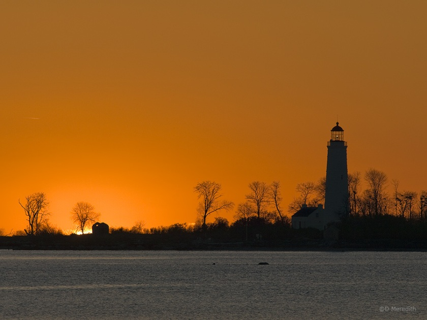 Silhouetted lighthouse at sunset.