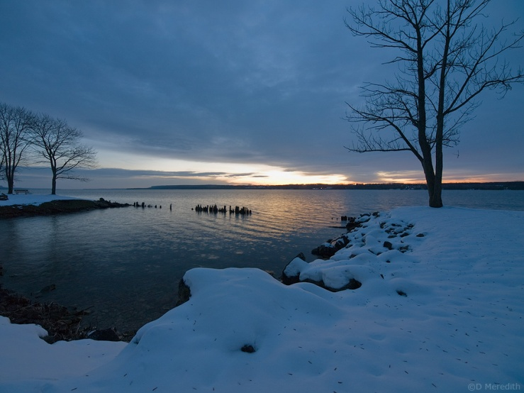 Snow covered shoreline at dawn.