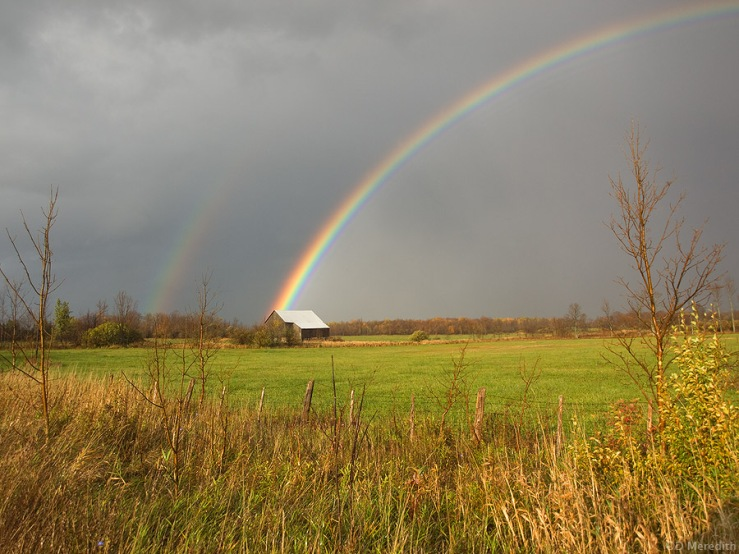 A double rainbow over an old barn.