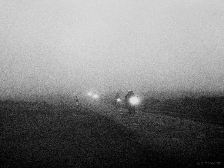 Motorcycles emerging from fog.
