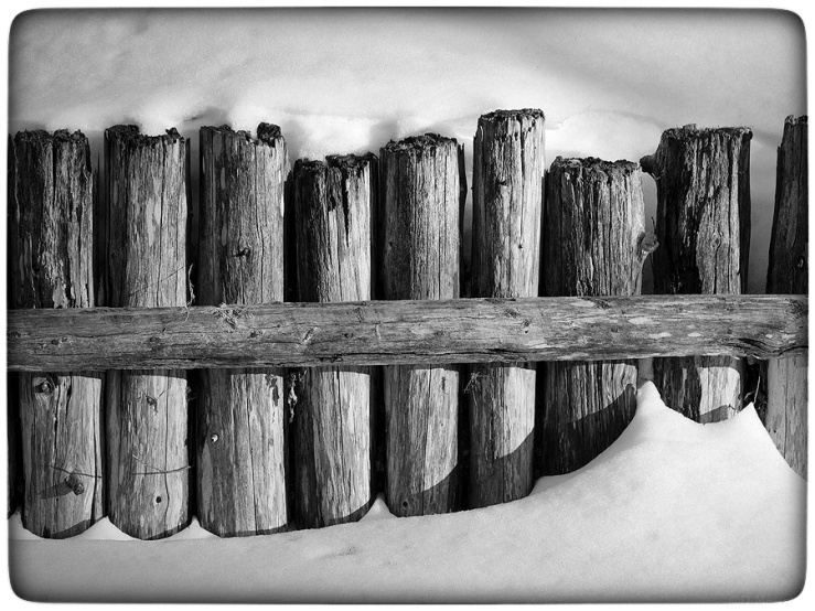 Fence buried in snow.