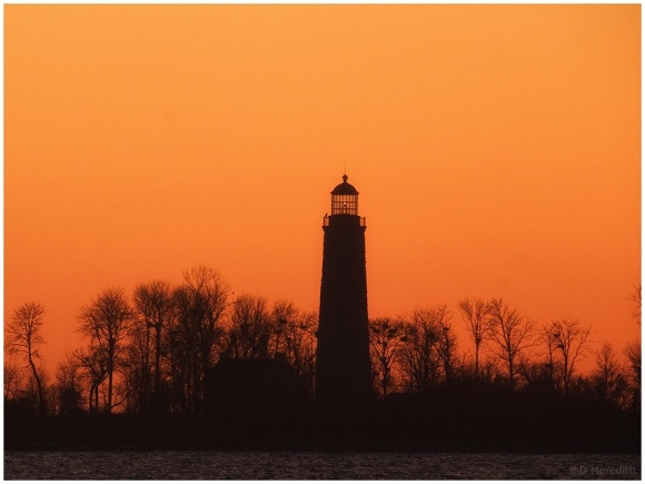 Lighthouse silhouetted against an orange sky.